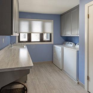 Foto di una sala lavanderia bohémian di medie dimensioni con lavello da incasso, ante con riquadro incassato, ante grigie, top in laminato, pareti blu, pavimento in gres porcellanato, lavatrice e asciugatrice affiancate, pavimento grigio e top grigio