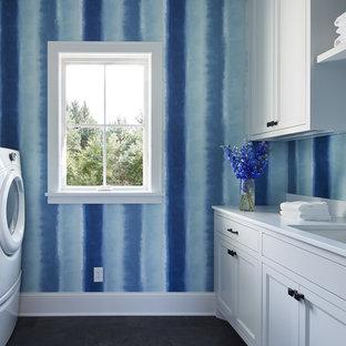 Стильный дизайн: отдельная, параллельная прачечная среднего размера в стиле кантри с белыми фасадами, полом из сланца, со стиральной и сушильной машиной рядом, врезной раковиной, столешницей из кварцевого агломерата, белой столешницей, фасадами с утопленной филенкой и синими стенами - последний тренд