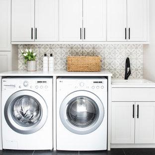 Modelo de cuarto de lavado lineal, clásico renovado, con fregadero encastrado, armarios estilo shaker, puertas de armario blancas, paredes grises, lavadora y secadora juntas, suelo negro y encimeras blancas