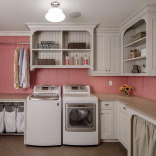 Foto på en vintage l-formad tvättstuga enbart för tvätt, med en undermonterad diskho, beige skåp, rosa väggar, en tvättmaskin och torktumlare bredvid varandra och luckor med profilerade fronter