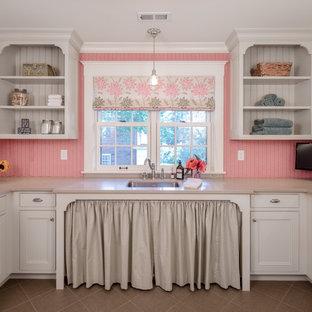 Idee per una grande lavanderia multiuso tradizionale con lavello sottopiano, ante a filo, ante bianche, top in superficie solida, pareti rosa, pavimento con piastrelle in ceramica e lavatrice e asciugatrice affiancate