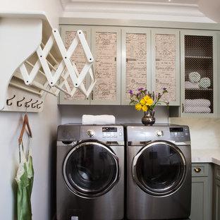 Inredning av en klassisk tvättstuga enbart för tvätt, med luckor med infälld panel, en tvättmaskin och torktumlare bredvid varandra och svart golv