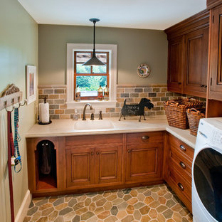 Mid-sized mountain style l-shaped travertine floor and beige floor dedicated laundry room photo in Other with an integrated sink, medium tone wood cabinets, solid surface countertops, gray walls and recessed-panel cabinets