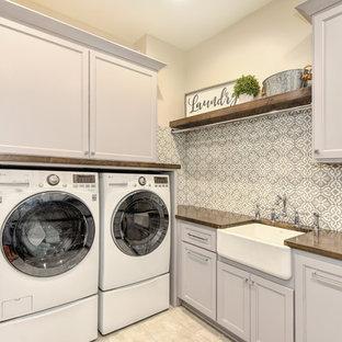 Lantlig inredning av en bruna l-formad brunt tvättstuga enbart för tvätt, med en rustik diskho, vita skåp, träbänkskiva, vita väggar, en tvättmaskin och torktumlare bredvid varandra och beiget golv