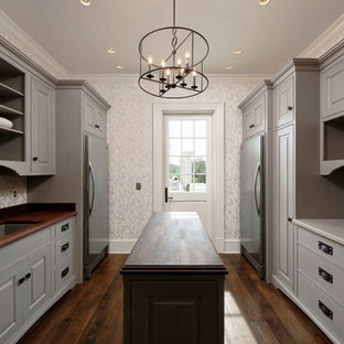 Inspiration for a huge timeless galley dark wood floor and brown floor utility room remodel in DC Metro with beaded inset cabinets, gray cabinets, wood countertops, a side-by-side washer/dryer, an undermount sink and white walls