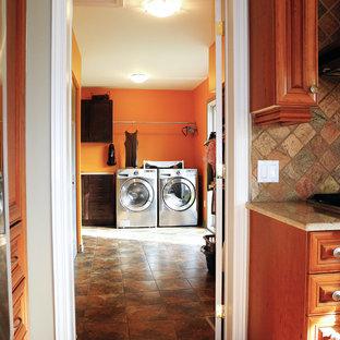 Aménagement d'une grande buanderie linéaire moderne multi-usage avec un placard avec porte à panneau encastré, des portes de placard en bois sombre, des machines côte à côte, un évier posé et un mur orange.