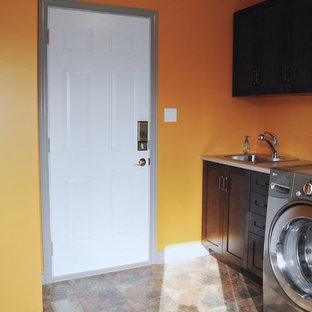Cette image montre une grande buanderie linéaire minimaliste multi-usage avec un évier posé, un placard avec porte à panneau encastré, des portes de placard en bois sombre, un mur orange et des machines côte à côte.