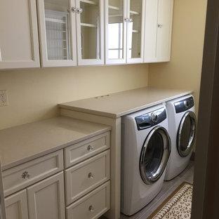 Ejemplo de lavadero multiusos y de galera, ecléctico, de tamaño medio, con armarios con paneles empotrados, puertas de armario blancas, encimera de cuarzo compacto, paredes amarillas, suelo de baldosas de porcelana y lavadora y secadora juntas