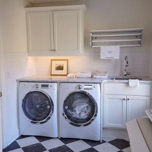 Exempel på en mellanstor klassisk grå linjär grått tvättstuga enbart för tvätt, med en undermonterad diskho, skåp i shakerstil, vita skåp, granitbänkskiva, vita väggar, en tvättmaskin och torktumlare bredvid varandra och flerfärgat golv