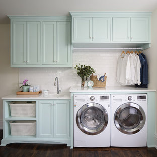 Mid-sized elegant single-wall dark wood floor and brown floor dedicated laundry room photo in Nashville with an undermount sink, turquoise cabinets, quartz countertops, a side-by-side washer/dryer, white countertops, recessed-panel cabinets and beige walls