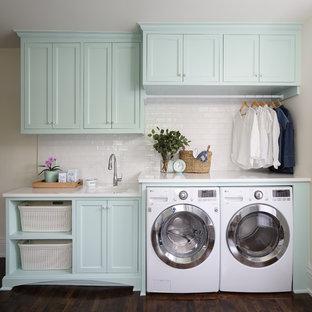 Immagine di una sala lavanderia tradizionale di medie dimensioni con lavello sottopiano, ante turchesi, top in quarzo composito, parquet scuro, lavatrice e asciugatrice affiancate, pavimento marrone, top bianco, ante con riquadro incassato e pareti beige