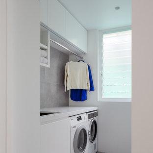 Foto di una piccola lavanderia contemporanea con lavello sottopiano, top in quarzo composito, lavatrice e asciugatrice affiancate, ante lisce, ante bianche, paraspruzzi grigio, pareti bianche, pavimento grigio e top bianco