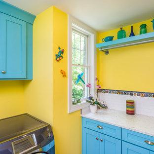 Inspiration för klassiska l-formade beige tvättstugor enbart för tvätt, med skåp i shakerstil, blå skåp, gula väggar och en tvättmaskin och torktumlare bredvid varandra