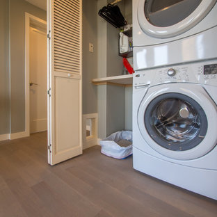 Laundry closet - small transitional single-wall medium tone wood floor laundry closet idea in Seattle with solid surface countertops, a stacked washer/dryer and gray walls