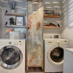 Ispirazione per una piccola sala lavanderia country con ante con finitura invecchiata, pareti grigie, pavimento in legno massello medio, lavatrice e asciugatrice affiancate e pavimento grigio