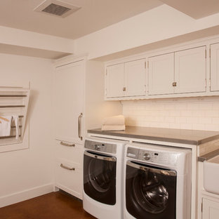 Inspiration for a mid-sized transitional u-shaped dedicated laundry room in Seattle with a farmhouse sink, shaker cabinets, white cabinets, zinc benchtops, white walls, concrete floors and a side-by-side washer and dryer.
