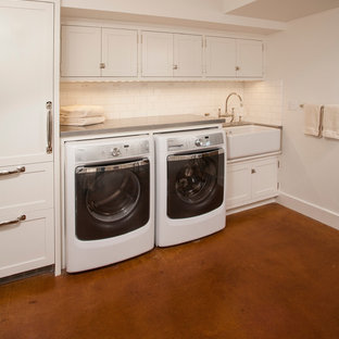 This is an example of a mid-sized transitional u-shaped dedicated laundry room in Seattle with a farmhouse sink, shaker cabinets, white cabinets, zinc benchtops, white walls, concrete floors and a side-by-side washer and dryer.