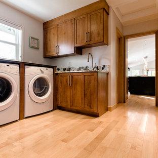 Esempio di una sala lavanderia chic di medie dimensioni con ante in stile shaker, ante in legno scuro, top in granito, pareti bianche, parquet chiaro e lavatrice e asciugatrice affiancate