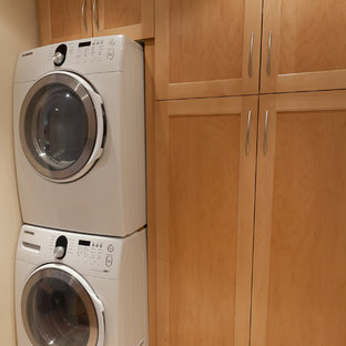 Inspiration for a mid-sized timeless single-wall dedicated laundry room remodel in San Diego with shaker cabinets, light wood cabinets and a stacked washer/dryer