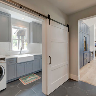 This is an example of a farmhouse single-wall separated utility room in Denver with a belfast sink, shaker cabinets, grey cabinets, white walls, a side by side washer and dryer, grey floors and white worktops.