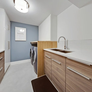 This is an example of a mid-sized contemporary galley dedicated laundry room in Calgary with a double-bowl sink, flat-panel cabinets, medium wood cabinets, white walls, a side-by-side washer and dryer, white floor and white benchtop.