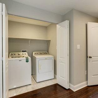Ispirazione per una piccola sala lavanderia classica con ante a persiana, pareti grigie, pavimento con piastrelle in ceramica, lavatrice e asciugatrice affiancate e pavimento bianco