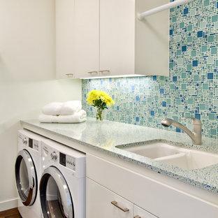 Idéer för en modern turkosa tvättstuga, med en dubbel diskho, släta luckor, vita skåp, bänkskiva i terrazo, en tvättmaskin och torktumlare bredvid varandra och vita väggar