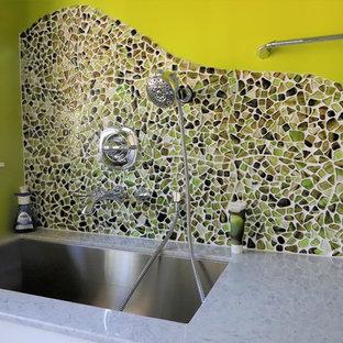 Inredning av ett modernt stort flerfärgad linjärt flerfärgat grovkök, med en allbänk, släta luckor, vita skåp, bänkskiva i kalksten, gröna väggar, vinylgolv, en tvättmaskin och torktumlare bredvid varandra och flerfärgat golv