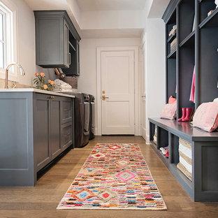 Imagen de lavadero multiusos y en L, ecléctico, grande, con armarios con paneles empotrados, puertas de armario grises, paredes blancas, suelo de madera clara, lavadora y secadora juntas y suelo marrón
