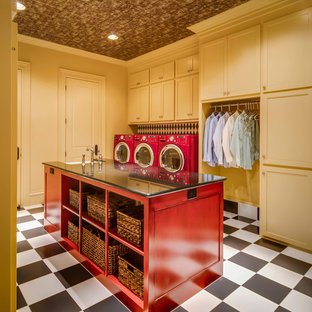 This is an example of a large traditional separated utility room in Austin with shaker cabinets, yellow cabinets, granite worktops, yellow walls, ceramic flooring, a side by side washer and dryer and a belfast sink.