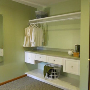 This is an example of a large traditional l-shaped utility room in Other with shaker cabinets, white cabinets, laminate countertops, green walls, carpet, a side by side washer and dryer and green floors.