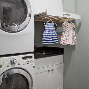 Esempio di una lavanderia multiuso classica di medie dimensioni con lavello sottopiano, ante in stile shaker, ante bianche, top in granito, pareti grigie, pavimento con piastrelle in ceramica, lavatrice e asciugatrice a colonna e pavimento grigio