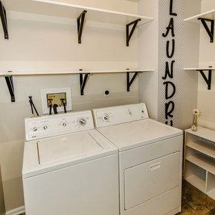Bild på en liten vintage tvättstuga enbart för tvätt, med en allbänk, grå väggar, vinylgolv och en tvättmaskin och torktumlare bredvid varandra