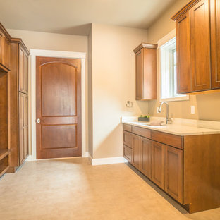 Inspiration for a large contemporary separated utility room in Denver with a submerged sink, raised-panel cabinets, dark wood cabinets, marble worktops, beige walls, ceramic flooring, a side by side washer and dryer, beige floors and white worktops.