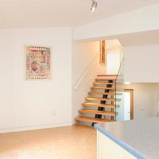 Esempio di una lavanderia multiuso di medie dimensioni con ante lisce, ante in legno chiaro, top in laminato, pareti bianche, pavimento in sughero e lavatrice e asciugatrice affiancate
