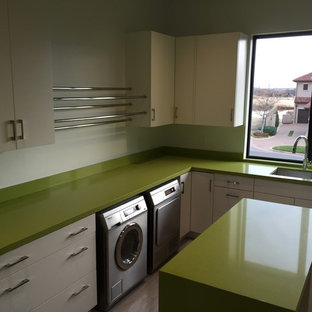 Photo of a large contemporary u-shaped utility room in Oklahoma City with a submerged sink, flat-panel cabinets, white cabinets, engineered stone countertops, white walls, ceramic flooring, a side by side washer and dryer, grey floors and green worktops.