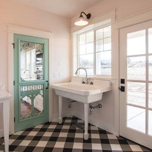 Неиссякаемый источник вдохновения для домашнего уюта: маленькая п-образная универсальная комната в стиле кантри с раковиной в стиле кантри, розовыми стенами, полом из керамической плитки, со стиральной и сушильной машиной рядом и черным полом
