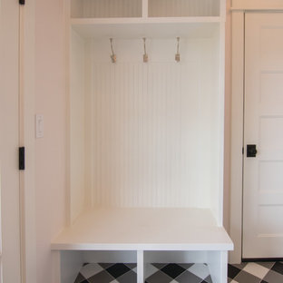 Photo of a small country u-shaped utility room in Other with a farmhouse sink, pink walls, ceramic floors, a side-by-side washer and dryer and black floor.