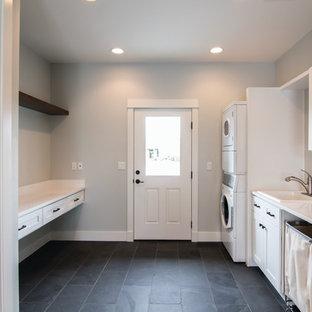 Неиссякаемый источник вдохновения для домашнего уюта: большая параллельная универсальная комната в стиле кантри с накладной раковиной, фасадами в стиле шейкер, белыми фасадами, столешницей из кварцевого агломерата, синими стенами, полом из сланца, с сушильной машиной на стиральной машине и бежевым полом