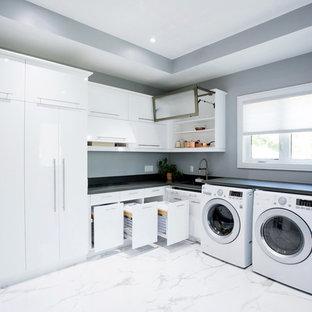 Foto di una grande sala lavanderia minimalista con lavello sottopiano, ante lisce, ante bianche, top in quarzo composito, pareti grigie, pavimento in marmo, lavatrice e asciugatrice affiancate, pavimento bianco e top grigio
