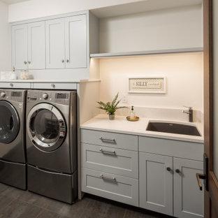Immagine di una sala lavanderia tradizionale di medie dimensioni con lavello sottopiano, ante in stile shaker, ante grigie, top in quarzo composito, pareti bianche, pavimento in gres porcellanato, lavatrice e asciugatrice affiancate, pavimento grigio e top bianco