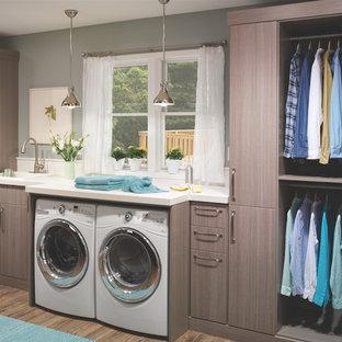 Inspiration för en mellanstor vintage linjär liten tvättstuga, med en nedsänkt diskho, släta luckor, bruna skåp, laminatbänkskiva, grå väggar, mellanmörkt trägolv, en tvättmaskin och torktumlare bredvid varandra och brunt golv