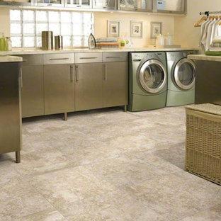 Exempel på en mellanstor klassisk l-formad tvättstuga enbart för tvätt, med luckor med glaspanel, skåp i rostfritt stål, marmorbänkskiva, beige väggar, klinkergolv i keramik och en tvättmaskin och torktumlare bredvid varandra