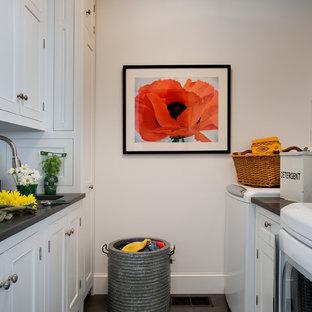 Inredning av en lantlig tvättstuga, med bänkskiva i täljsten, vita skåp, vita väggar, skiffergolv och grått golv
