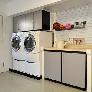 Idéer för ett stort modernt linjärt grovkök, med släta luckor, grå skåp, laminatbänkskiva, vita väggar, betonggolv, en tvättmaskin och torktumlare bredvid varandra och beiget golv