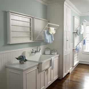 Aménagement d'une buanderie classique avec des portes de placard blanches, un plan de travail blanc et un évier posé.