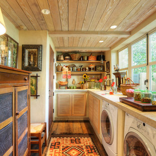 Example of a country l-shaped utility room design in Sacramento with louvered cabinets