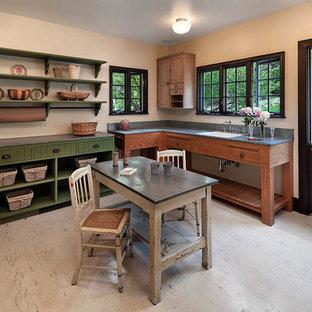 Inredning av ett lantligt stort grå u-format grått grovkök, med en nedsänkt diskho, öppna hyllor, gröna skåp, bänkskiva i koppar, beige väggar och en tvättmaskin och torktumlare bredvid varandra