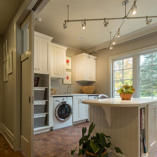 Foto på ett stort vintage grovkök, med en nedsänkt diskho, vita skåp, bänkskiva i koppar, grå väggar, korkgolv och en tvättmaskin och torktumlare bredvid varandra