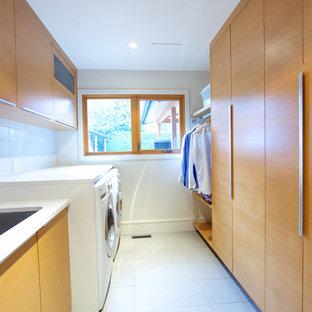 Пример оригинального дизайна: большая отдельная, параллельная прачечная в современном стиле с врезной раковиной, плоскими фасадами, фасадами цвета дерева среднего тона, со стиральной и сушильной машиной рядом, белыми стенами и полом из керамической плитки